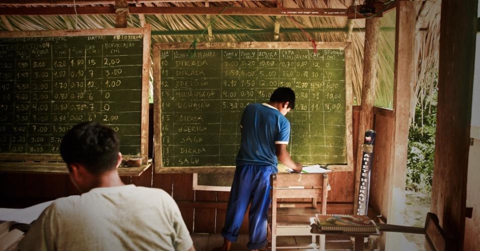 Índio tuiuca transcreve medições de árvores pesquisadas em aula em escola na comunidade indígena de São Pedro (AM)