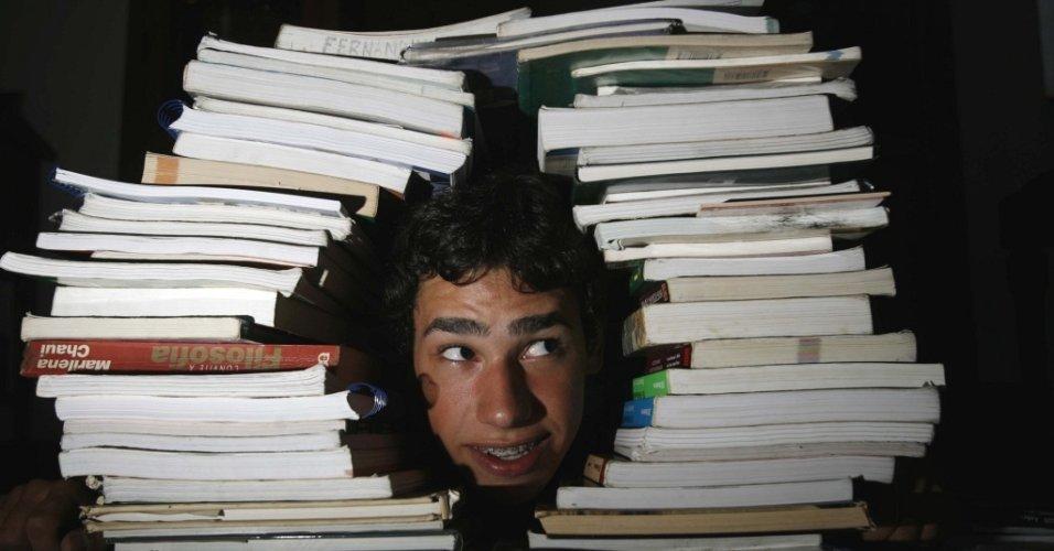 O estudante Maurício Saraiva Pacheco, que está fazendo cursinho pela segunda vez para entrar no ITA, posa para foto entre livros. Foto de 2008